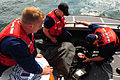 U.S. Coast Guard Petty Officers 3rd Class Daniel Ladnier and William Perdue watch as Petty Officer 1st Class Terry Bailey checks Canadian coast guardsman Stephen Harrie during a search and rescue drill off 090826-G-JG957-004.jpg