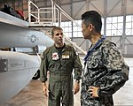 U.S. Navy Cmdr. Dave Kurtz, left, the executive officer of Electronic Attack Squadron (VAQ) 132, discusses the EA-18G Growler aircraft with Japan Air Self Defense Force Col. Kenji Minami, assigned to 120823-N-VZ328-021.jpg