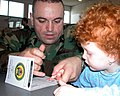 US Navy 031205-N-4178C-001 Master-at-Arms 2nd Class Noel Ramos from Camden, N.J. fingerprints a young toddler during the Health, Fitness and Safety Fair.jpg