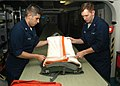 US Navy 040617-N-1513W-011 Aircrew Survival Equipmentman 3rd Class Vincente Perez (left) and Aircrew Survival Equipmentman 1st Class Gregory Majors service an A-P22P-11 Parachute.jpg