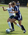 US Navy 040829-N-9694M-002 U.S. Naval Academy Midshipman 3rd Class Meggie Curran races to keep the ball away from George Mason University's Danielle McDonald during a regular season soccer match.jpg