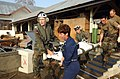 US Navy 050302-N-6665R-029 Cmdr. Karen McDonald, center, a U.S. Navy nurse, is assisted by members of the German military as they carry an Indonesian patient to an awaiting U.S. Navy helicopter.jpg