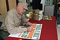 US Navy 060107-M-8440C-061 Retired U.S. Marine Corps Gunnery Sgt. R. Lee Ermey signs a poster, while visiting the Hansen Post Exchange (PX) during his Pacific Mail Call book signing tour.jpg