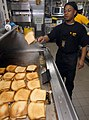 US Navy 060822-N-4856C-052 Culinary Specialist 3rd Class James M. Freeman prepares grilled ham and cheese sandwiches in the chief petty officers galley aboard the amphibious assault ship USS Iwo Jima (LHD 7).jpg