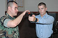 US Navy 070814-N-8848T-033 Gas Turbine System Technician (Mechanical) 2nd Class T. A. Keith, from Round Rock, Texas, instructs Seaman Travis Carter, from Rolla, Mo., on the proper stance when firing a 9mm pistol at Recruit Tra.jpg