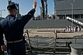 US Navy 110922-N-EA192-023 Lt. Michael Bono waves goodbye to members of the Japan Self-Defense Force as the the guided-missile destroyer USS Mustin.jpg