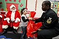 US Navy 111219-N-HW977-225 Chief Petty Officer Andra Hall, right, assigned to Naval Surface Warfare Center (NSWC) Corona, gives a gift to a child d.jpg