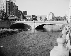 A concrete arch bridge crosses a river in two arch spans, with mid-size buildings visible in the distance.