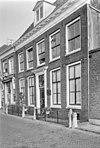 foto van Pand met gevel met rechte kroonlijst, houten deuromlijsting, kroonlijst met metopen