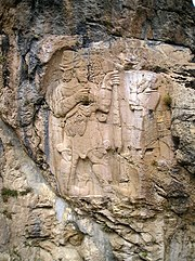 The photograph shows a sculpted rock: a bas-relief appears in grey-beige on a blue-gray rock stained with dark grey streaks.  The Hittite king is on the left.  He is bearded and holding a branch with two grapes.  Facing him, the god has lost his head and his feet because of the ravages of time