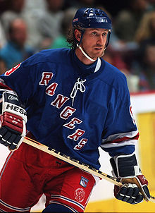 "A hockey player stares intently to his left. He is in full uniform with a blue helmet and jersey, and red pants. The jersey has the word ""RANGERS"" spelled diagonally down his chest."