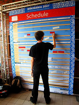 Schedule - A volunteer adjusts the schedule board at Wikimania 2007. The board indicates the times and locations at which events will take place, thus assisting participants in deciding which events they can attend.