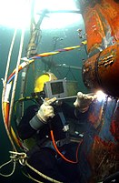 Helmeted surface-supplied diver using a coated electrode to arc-weld a steel patch to the underwater hull of a landing craft.