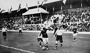 Football at the 1912 Summer Olympics - The Final: Denmark's captain Nils Middelboe (dark shirt) against two opponents