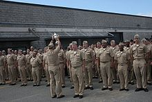 A sailor holds up a trophy in front of a formation of sailors