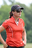 Woman golfer with standing with hat and hands on hips