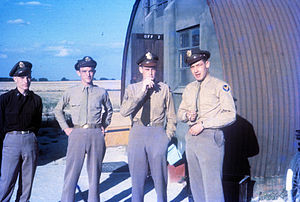 "RAF Fowlmere - Four United States Army Air Force officers standing in front of a Nissen hut. Handwritten on slide: ""Paul Fickel, Bernie Allen, Anthony Hawkins, Ethelbert Graham 503FS Fowlmere James G. Robinson""."