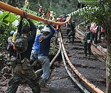Workers position a pipe amid muddy conditions in a jungle environment to pump water from the Tham Luang cave