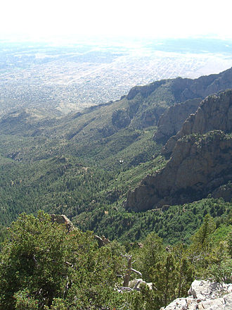 Cibola National Forest - View from Sandia Peak, in the Sandia Mountains. In the background is Albuquerque, New Mexico. In the center is a tramway car moving along the Sandia Peak Tramway.