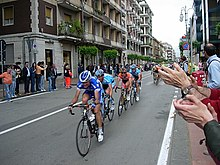 Various cyclists, clad in jerseys of different colors, speed down an open road. Spectators watch from the roadside, and cheer them on