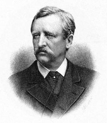 Head and shoulders portrait of a middle-aged man, facing half-left. He has dark, neatly brushed hair, a heavy moustache, and is wearing a dark, formal jacket.