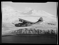 A PBY-5A Catalina patrol bomber cruises against a backdrop of snow-clad mountains in Aleutian Islands, searching for... - NARA - 520976.jpg