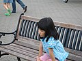 A girl sitting on a bench, Hokkaido, Japan; August 2009.jpg