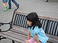 A girl sitting on a bench, Hokkaido, Japan; August 2009.jpg