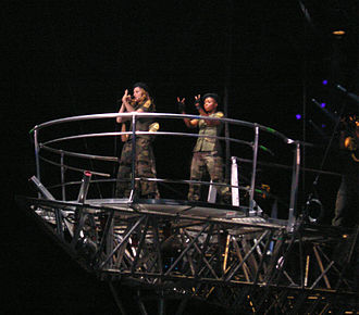 "American Life (song) - Madonna and her dancers performing ""American Life"" on top of a suspended catwalk on the Re-Invention World Tour in 2004"