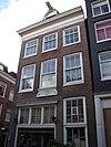 foto van Huis met voorgevel onder rechte lijst waarop een rondbogige dakkapel