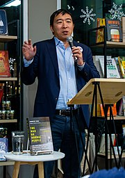 Yang is holding a microphone while gesturing and making a speech. His book, The War on Normal People, is displayed on a table in front of him.