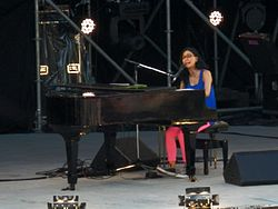 A woman with black glasses seated at a grand piano on a stage, wearing a blue singlet, pink tights and sneakers.
