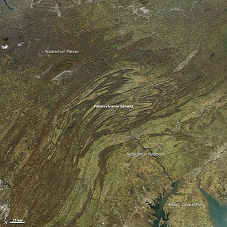 """Geology of the Appalachians - The """"Pennsylvania Salient"""" in the Appalachians, appears to have been formed by a large, dense block of mafic volcanic rocks that became a barrier and forced the mountains to push up around it. 2012 image from NASA's Aqua satellite."""