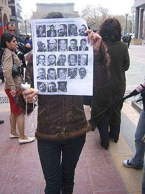 2008 Armenian presidential election protests - In a silent protest, a young woman holds pictures of some of the 106 political prisoners