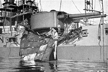 The side of the ship has been badly caved in by a large, bent piece of steel plate thrown by the explosion.