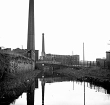 A canal leading towards two mills with tall chimneys