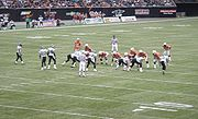 BC Lions quarterback Dave Dickenson calls out a play at the line of scrimmage in a game against the Saskatchewan Roughriders at BC Place. The Lions (wearing orange jerseys) have extra blockers in to counter a blitzing Saskatchewan defence.
