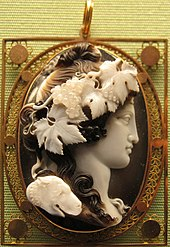 Brown and white stone cameo of a woman facing right with flowers and leaves in her hair