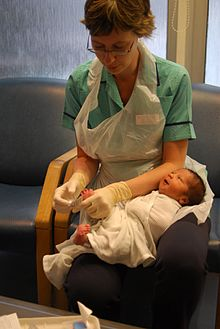 Photograph of a modern, British nurse caring for a baby