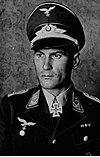 A man wearing a military uniform with an Iron Cross displayed at the front of his uniform collar.