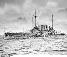 A battleship at sea with a smaller boat alongside