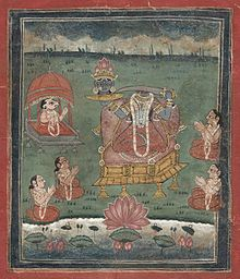 Depicted enthroned, a decapitated, dark-complexioned woman wearing a red/orange sari holds a sword in her left hand and her own severed head (with a lotus crown) on a platter in her right hand. Five seated devotees (including one with a ram's head) with folded hands surround her. A lake with a large lotus is in the foreground.