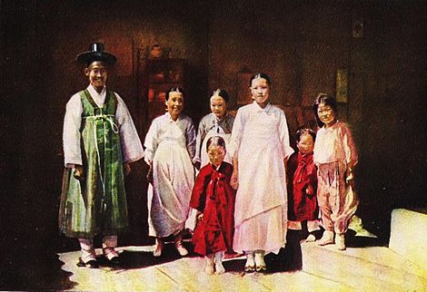 In this picture a Korean family is standing together. Three women are wearing dresses. Two boys are wearing long coats. One girl is wearing her pajamas. A fat man is wearing a bath robe, a rope around his chest, and a black cowboy hat that is too small for him.