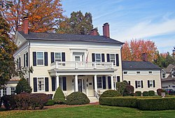 A pale yellow house with white trim, a black roof and shutters, for brick chimneys and a front porch with square pillars and a balcony on top. There is a lawn with manicured shrubbery in front, and behind it there are trees, most of which are in autumn color