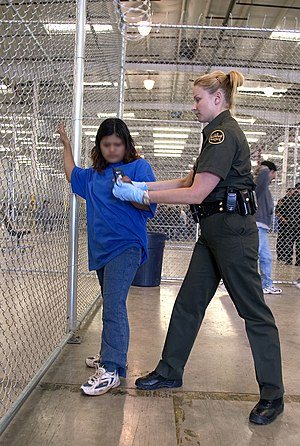 CBP Border Patrol agent conducts a pat down of...