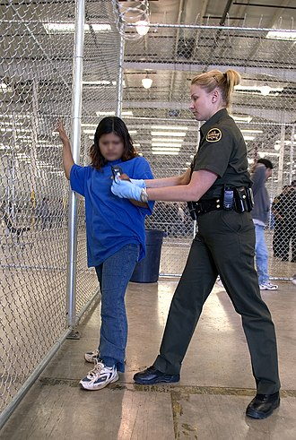 Immigration detention - A CBP Border Patrol agent with a female detainee in a holding facility.