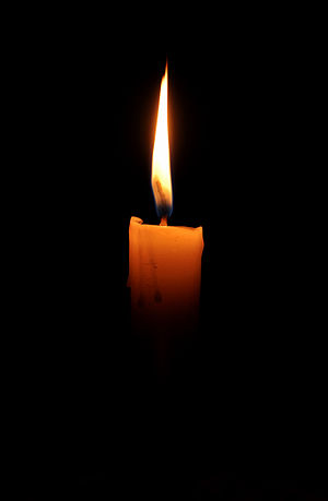 English: A lit candle in the dark Español: Una...