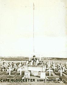 Service personnel with a padre at a memorial service. In the foreground are several graves marked with white crosses.