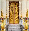 Carved door panels at Wat Haysoke on the side of the wat showing Nyak Koumphan battling Sinxay, Siho and Sangthong.jpg