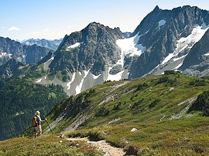 Photograph of snowy mountain peaks with a hiker in the bottom-left atop grassy terrain